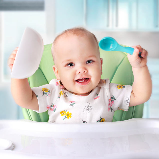 happy baby holding bowl and spoon in high chair