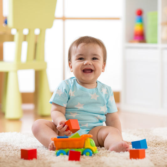 happy child playing with toys on the floor