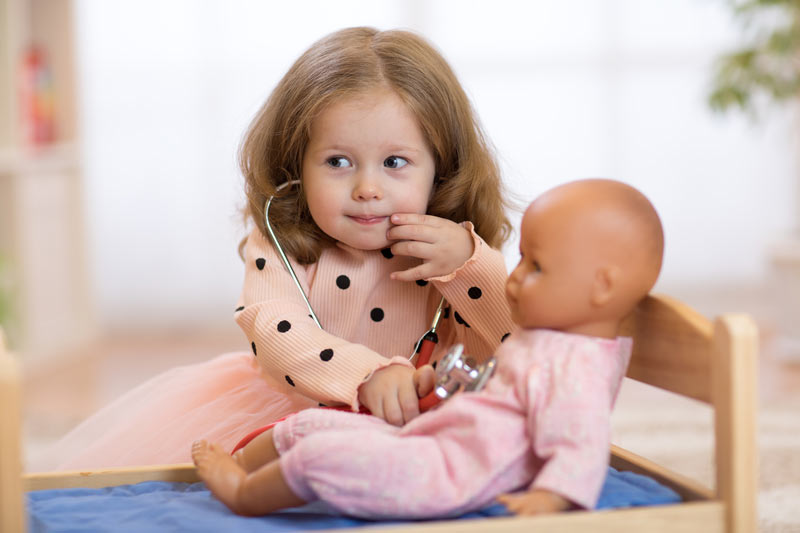 small cute girl playing doctors with a toy baby
